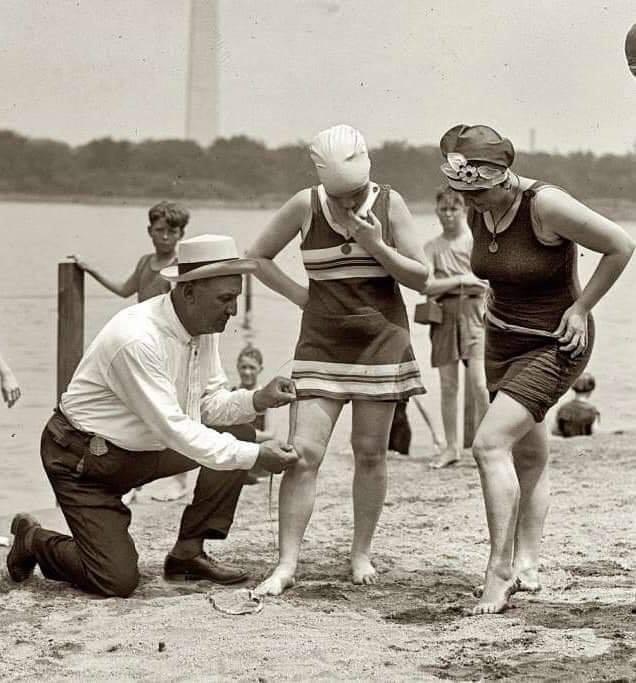 Un hombre midiendo la longitud de la falda de una bañista de principios del siglo XX